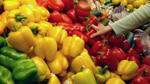 Woman selecting fresh red peppers in grocery store Footage