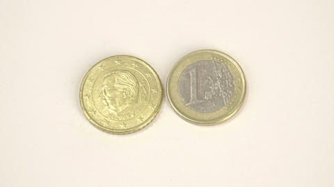 A gold plated coin and a 1 Belgium Euro coin Live Action