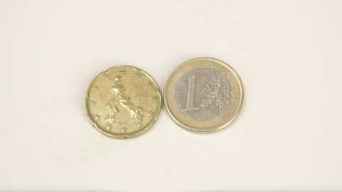 A bumpy sided Italy coin and a 1 Euro coin Footage