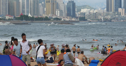 4k many people at crowded sandy beach.People swimming in sea,QingDao,China Live Action