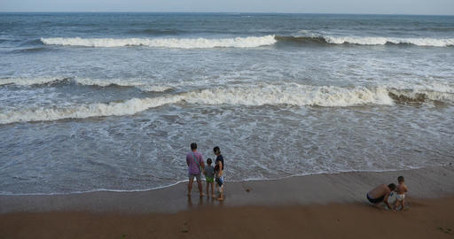 4k China Parents with children playing on the beach,wide ocean & big surge Footage