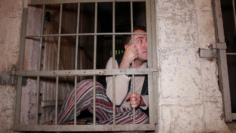 Mad prisoner looks through the bars Footage