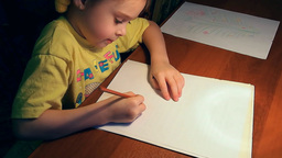 Cute little girl drawing with concentration on Footage