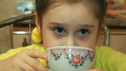 Cute little girl drinking tea and looking arou Footage