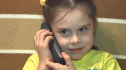 Cute little girl talking by telephone Footage