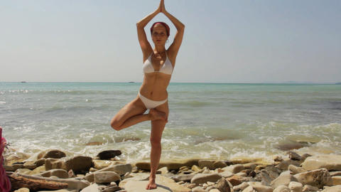 Young woman doing yoga exercises on beach Stock Video Footage