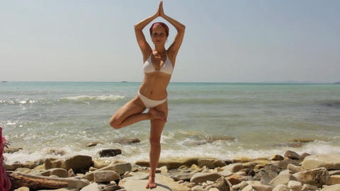 Young woman doing yoga exercises on beach Footage