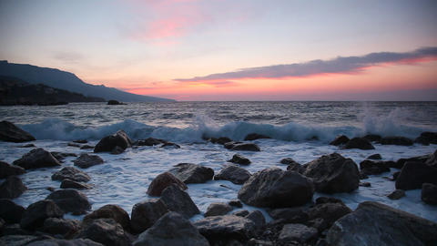 Waves break about stones at sunrise over the sea Footage