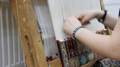Carpet weaving. Turk woman making a silk carpet Live Action