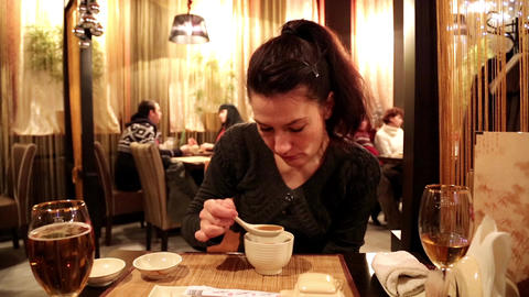 Woman eating miso soup in a Japanese restaurant Footage
