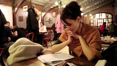 Woman reading in restaurant Footage