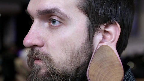 Man with big wooden flesh tunnel in ear Live Action