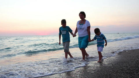 Family walks on the beach at sunset Stock Video Footage
