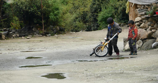 4k two little tibet boys play bicycle,china Footage