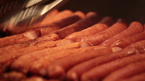Cook Overturns The Sausages Which Are Fried On A G stock footage