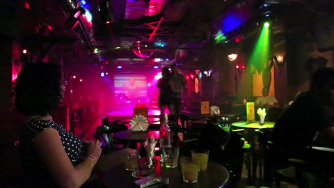 Woman sits at a table in a nightclub Footage