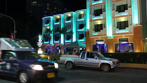 Road traffic near motel with blue night illumination in Pattaya, Thailand Footage