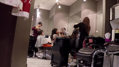 People having an haircut in a hairdressing salon w Footage