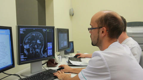two doctors watching the obtaining data from CT and MRI scanners (on dolly) Footage