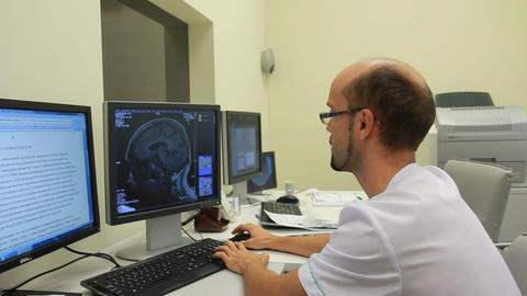The doctor watching a data from CT and MRI scanners (on dolly) Footage