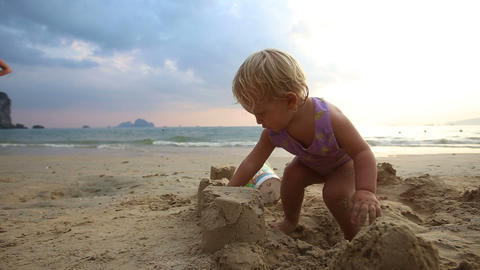 girl in purple swimsuit play in the sand Footage