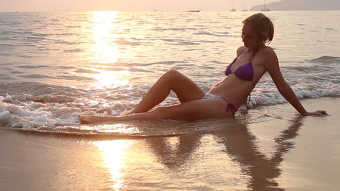 woman sit in sea wave at sunset Footage