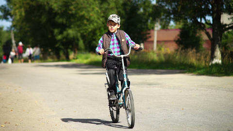 Boy riding bicycle in a village Footage