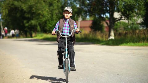 Boy riding bicycle in a village Stock Video Footage