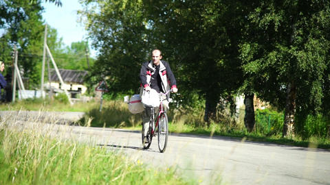 Man riding bicycle in a village Stock Video Footage