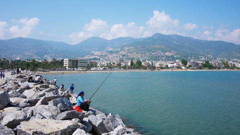 Fishers Sitting On Rocks In Alanya, Turkey stock footage