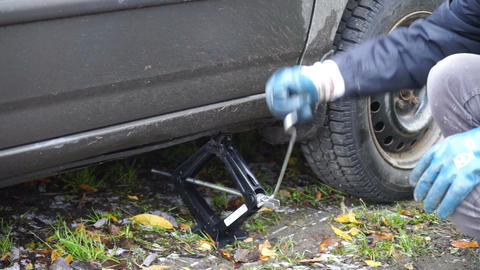 Man using a jack for putting car down Stock Video Footage