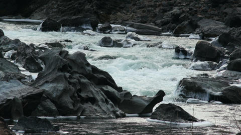 4K UHD Iced Black Rocks in a Mountain River Footage