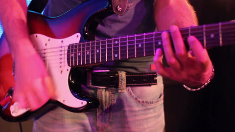 rock band: medium shot of a guitarist playing on electric guitar GIF