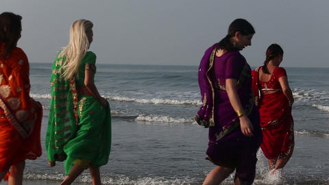 girls in indian clothes dancing in the sea Footage