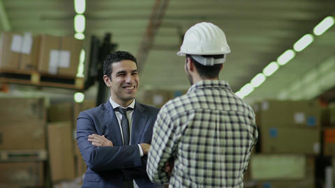 Manager And Worker Talking In Warehouse stock footage