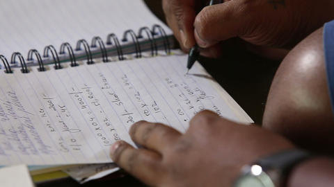 dark-skinned man writing notes with pan Footage