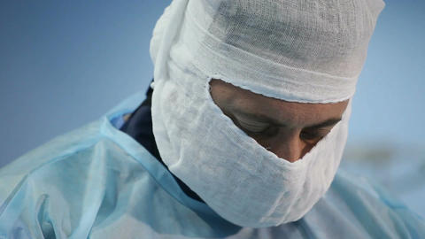 Close-up of a surgeon and then hands during insertion of needle into the vein Footage