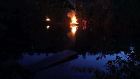 fire camp (view across the river, where the boat will be send burning) Footage
