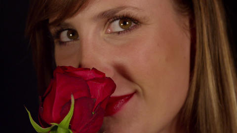 Smiling woman smelling red rose Stock Video Footage