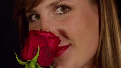 Smiling woman smelling red rose Live Action