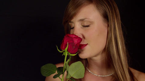 Young woman smelling fragrant red rose Live Action