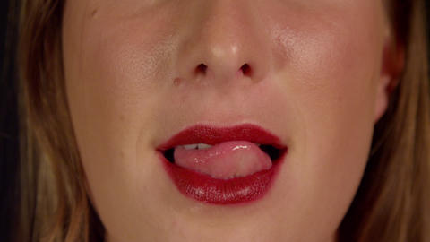 CLOSE UP SLOW MOTION: Female licks her red lips Footage