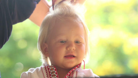 mother combing blonde small smiling girl closeup Footage