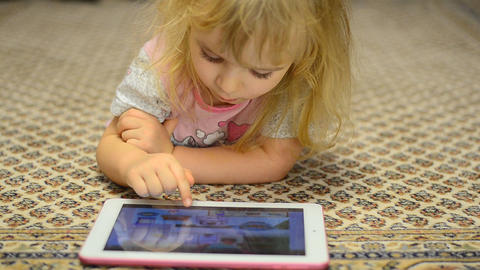 Cute Little Girl Works On Tablet Computer Lying On stock footage