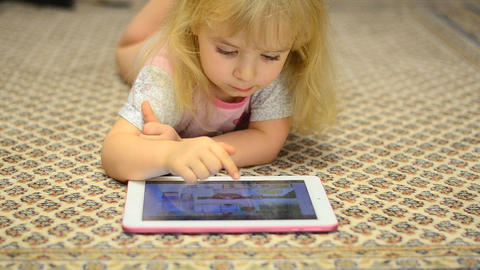 Baby Girl Playing On Tablet Computer Lying On Carp stock footage