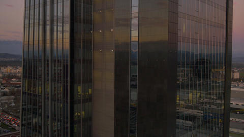 AERIAL: Flying around the skyscraper at dusk Footage