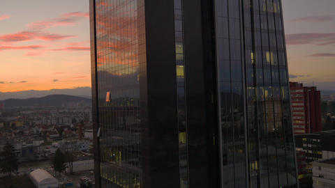AERIAL: Flying around glass office building at sun Footage
