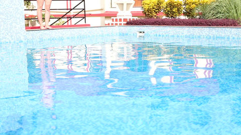 Girl Standing At Edge Of Hotel Pool Among Planting stock footage