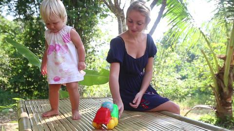 little blonde girl dance near her mother under tro Footage
