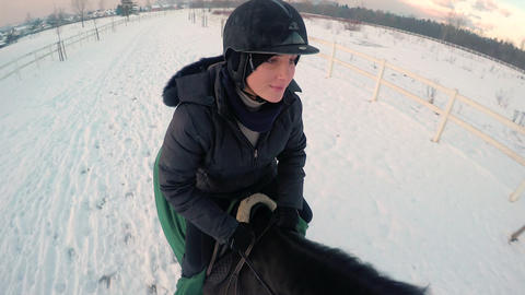 Young woman and big black horse galloping on snow Footage